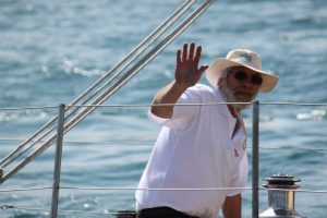 Guild member waving from deck of wooden yacht